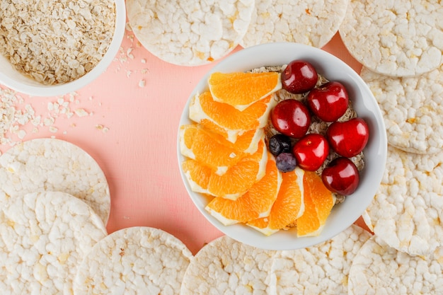 Oat flakes with orange, berries, cherry, rice cakes in bowl