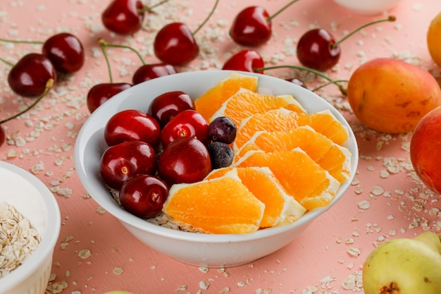 Oat flakes with pear, apricot, orange, cherry, berries in bowl