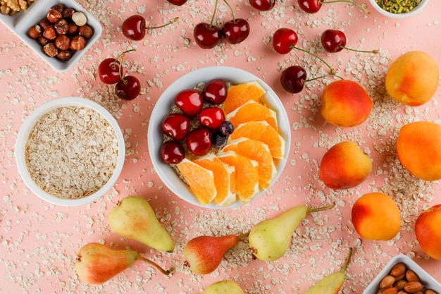 Oat flakes with pear, apricot, orange, cherry, nuts in bowls