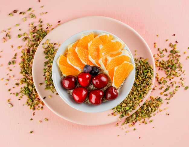 Oat flakes with pistachio, cherry, orange, berries, plate in a bowl