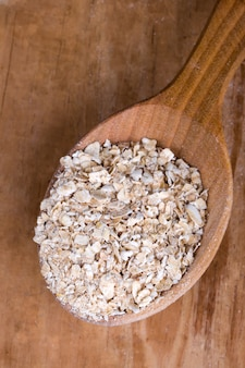 Oat flakes in wooden spoon closeup
