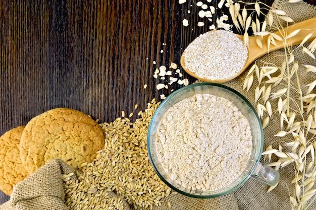 ガラスのボウルにオーツ麦粉、スプーンにふすまフレーク、木の板の背景に袋に入れてオーツ麦の茎とオートミールクッキー