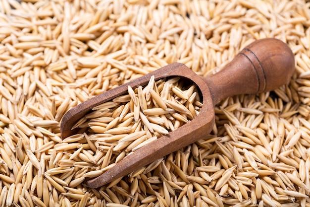 Зерна овса и деревянный совок как фон