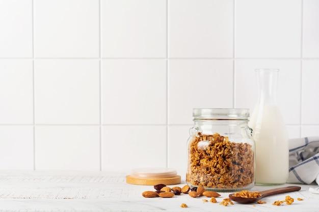 牛乳、ナッツ、ドライフルーツのボトル、明るいキッチンテーブルで健康的な朝食を準備するためのセラミックボウルを備えたオーツ麦グラノーラ。スカンジナビアの白いスタイル。セレクティブフォーカス。