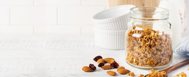 우유, 견과류 및 말린 과일 한 병이 담긴 귀리 그래 놀라, 밝은 식탁에서 건강한 아침 식사를 준비하기위한 세라믹 그릇. 스칸디나비아 화이트 스타일. 선택적 초점.