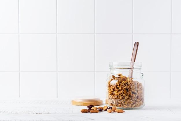 Овсяная мюсли с орехами и сухофруктами на ярком кухонном столе