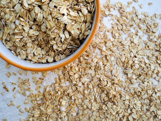 Oat groats or oat spike in wooden plate on homespun tablecloth, copy space, top view, selective focus