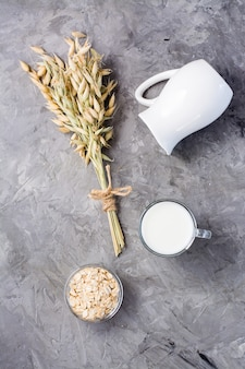 Oat milk in a cup, oatmeal and ears on a gray background. alternative to cow's milk. healthy eating. top and vertical  view