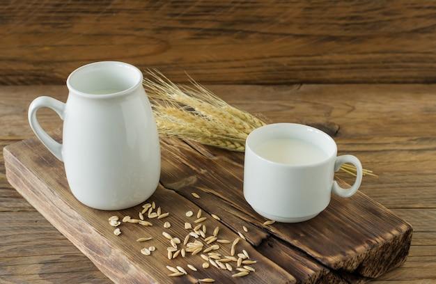 유리 투수에 귀리 우유와 나무 테이블에 컵에 오트밀.