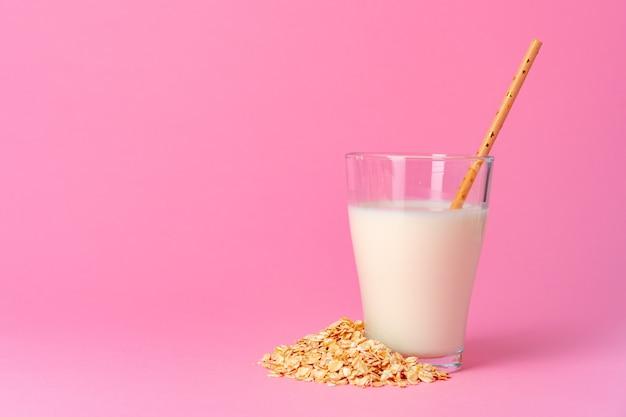 Овсяное молоко в стеклянной посуде и сухие овсяные хлопья на розовом фоне