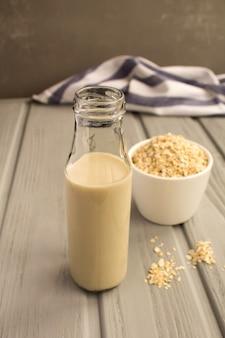 灰色の背景のガラス瓶にオーツ麦ミルク。健康的な飲み物。