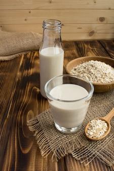素朴な木製の背景にガラスのオーツ麦ミルク。健康的な飲み物。