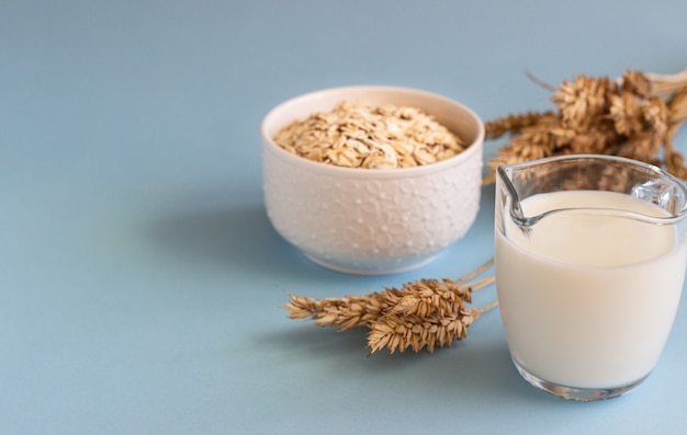 Oat milk in a jug and oats in a white ceramic bowl on a blue paper .