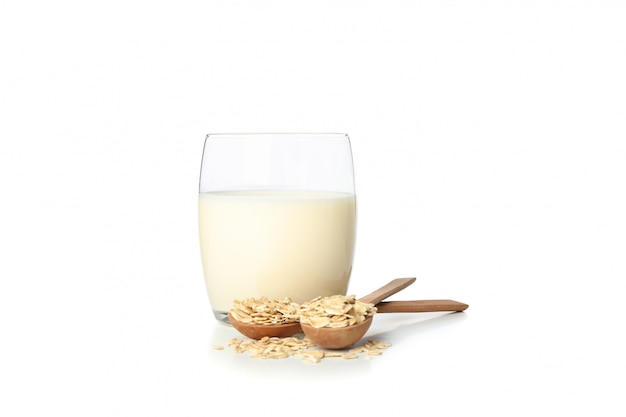 Oat milk and oatmeels in spoon isolated on white
