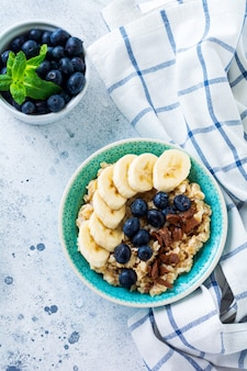 Oat porridge with banana, chocolate and fresh blueberry in a bowl on a light gray slate, stone or concrete surface