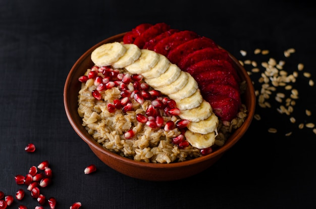 Oat porridge with banana, pomegranate seeds and opuntia cactus fruit.