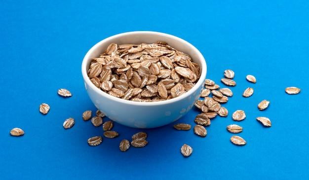 Oat rye flakes in bowl isolated on blue color