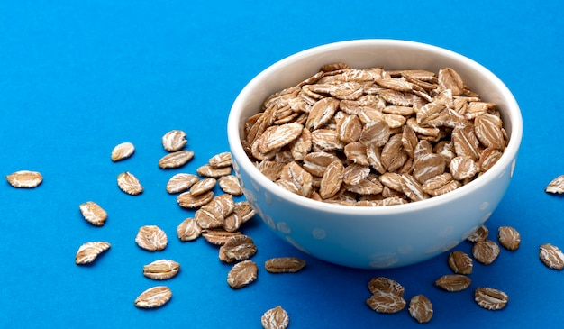Oat rye flakes in bowl isolated on blue