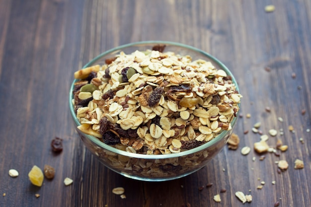 Oat with dry fruit in white bowl on brown backround