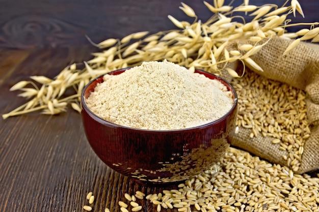 ボウルにオーツ麦粉、オーツ麦の入ったバッグ、ダークウッドの板の背景にオーツ麦の茎