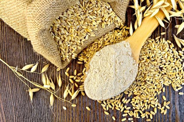 スプーンのオーツ麦粉、オーツ麦の袋、上の木の板の背景にオーツ麦の茎