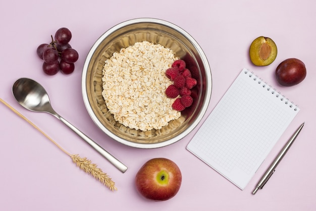 金属製のボウルにオートミールとラズベリー。メモ帳とペン。テーブルの上のブドウ、プラム、リンゴ。フラットレイ。ピンクの背景