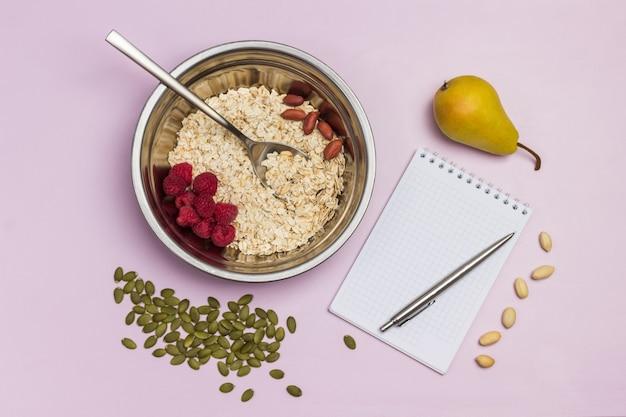 金属製のボウルにオートミールとラズベリー。メモ帳とペン。テーブルの上の梨とカボチャの種。フラットレイ。ピンクの背景