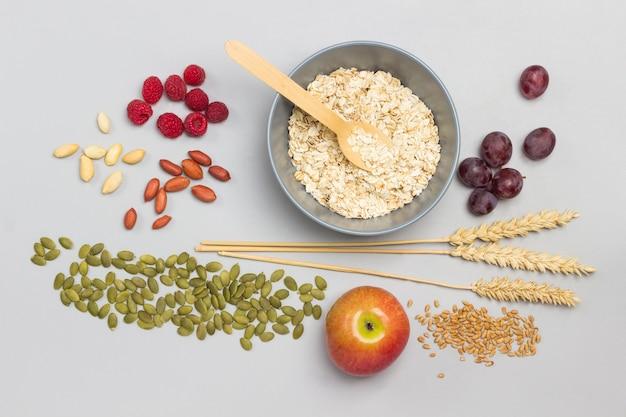灰色のボウルにオートミールとスプーン。テーブルの上の小麦、ラズベリーとブドウ、リンゴとカボチャの種の小穂。フラットレイ。灰色の背景