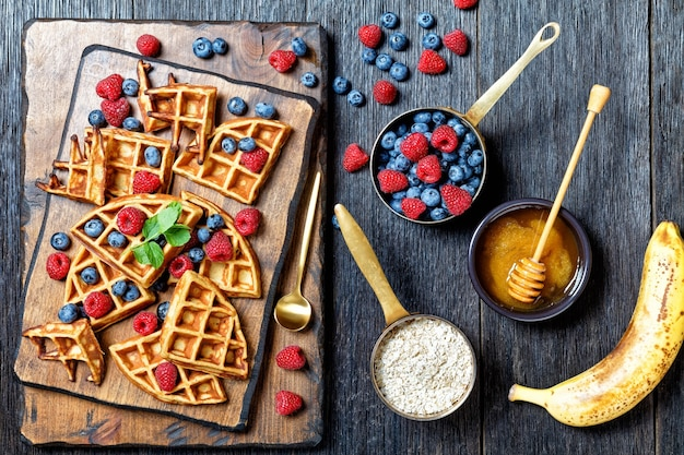 Oatmeal banana waffles served with berries and honey on a dark wooden cutting board on a wooden table, horizontal view from above, landscape view from abovef, flat lay