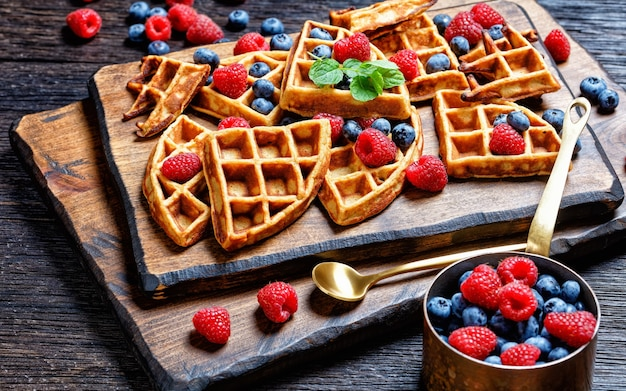 Oatmeal banana waffles served with berries and honey on a dark wooden cutting board on a wooden table, horizontal view from above, landscape view from above, close-up