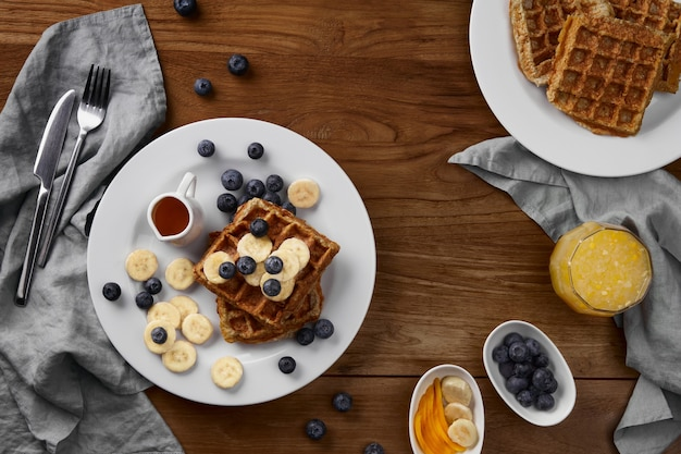 Oatmeal belgian waffles topped with banana and blueberry on rustic wooden table