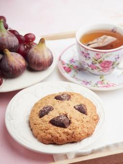 皿の上に花と新鮮な果物で飾られたお茶のカップの横にチョコレートチップとオートミールビスケット