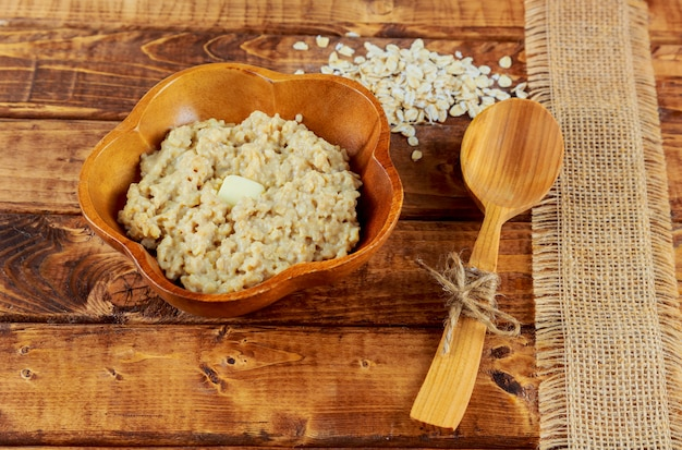 Oatmeal in black bowl and near on dark wooden table