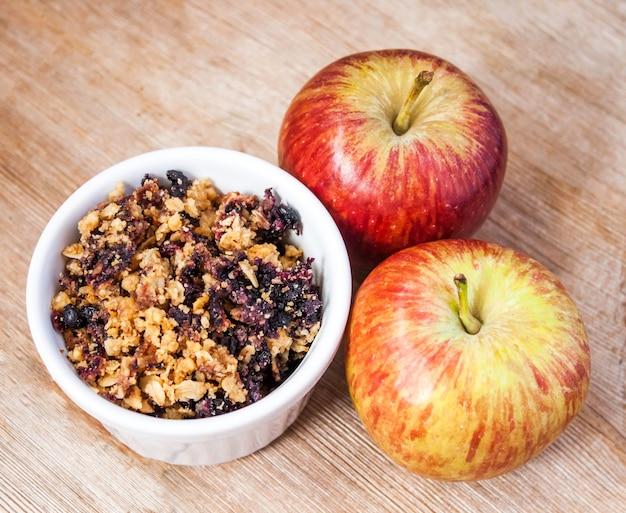 オートミールブルーベリーはセラミックボウルと2つのリンゴで崩れます