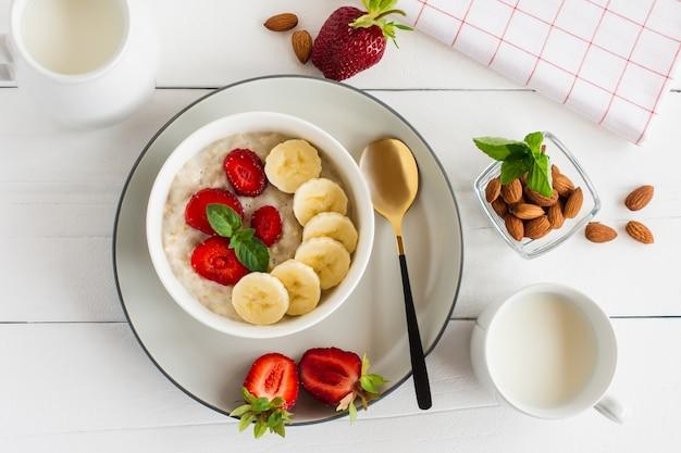 白いテーブルの上にバナナとイチゴ、ミルクグラスとオートミールボウル。健康的な有機食品。