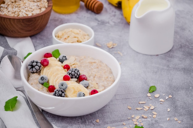 Oatmeal in a bowl with banana, frozen berries, almond petals, mint leaves and honey on a gray stone surface