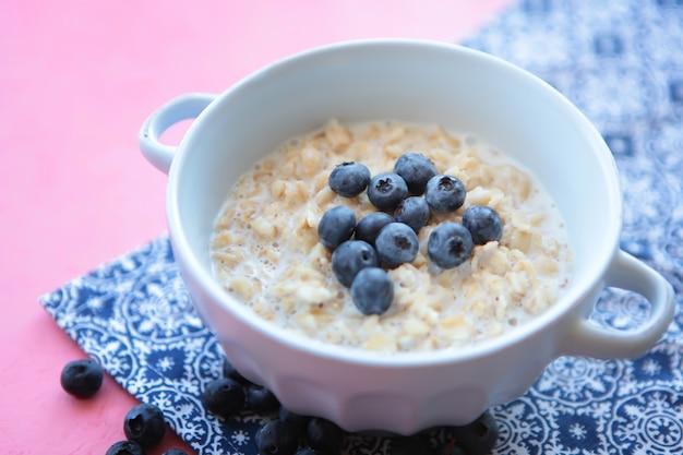 Овсяная тарелка с черникой для здорового завтрака голубая салфетка и розовый фон питания
