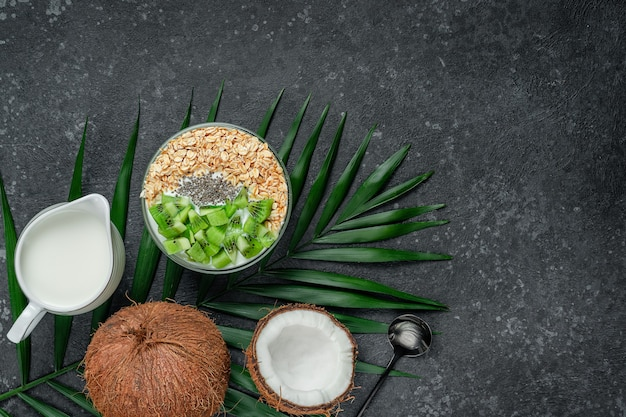 Oatmeal bowl with coconut milk, kiwi and chia seeds, copy space. vegetarian food concept.