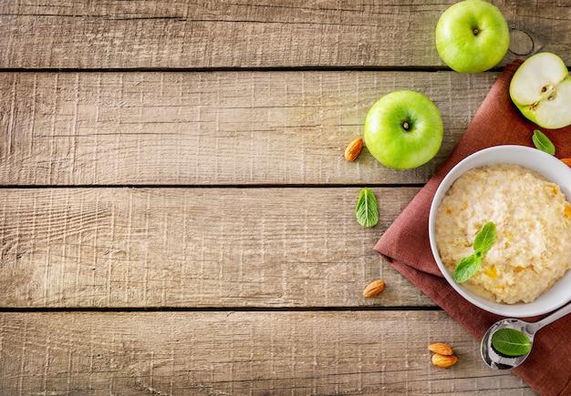 ミントの葉と木製の背景にリンゴとオートミールボウル。上面図。スペースをコピーします。
