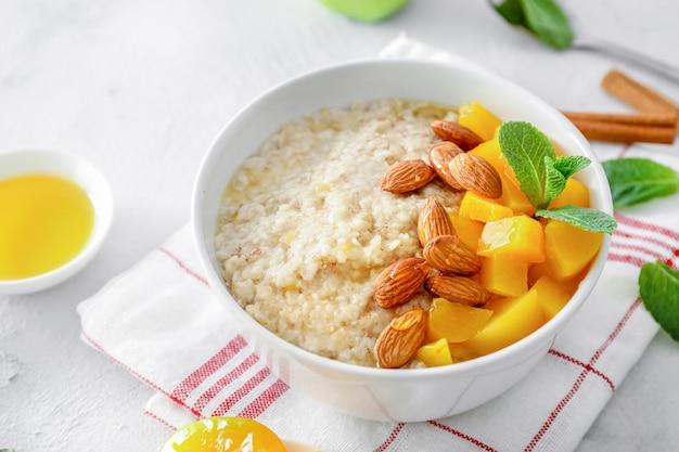 ミントの葉、シナモン、桃の部分、アーモンドナッツ、白い背景に蜂蜜とオートミールボウル。