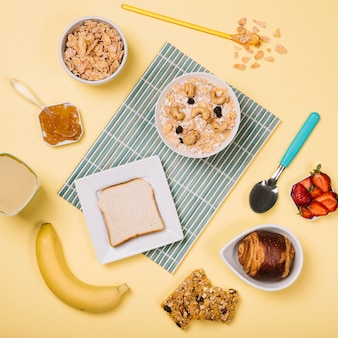 Oatmeal in bowl with toast and fruits on table
