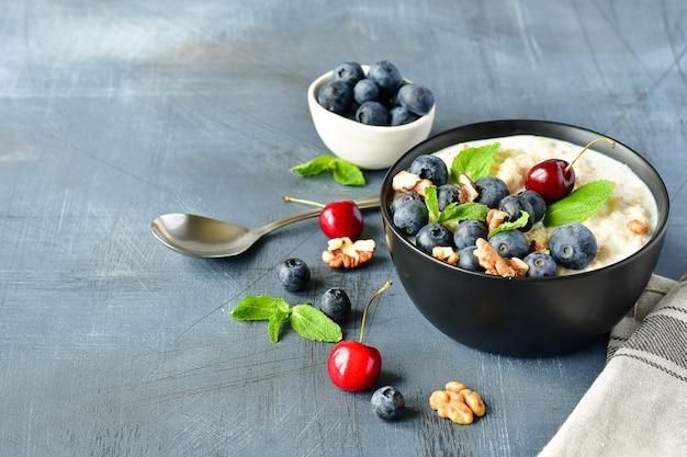 Oatmeal cereal porridge with fresh berries in black bowl.