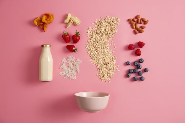 Овсяные хлопья, аппетитные свежие ягоды, сухофрукты, растительное молоко, орехи и миска для приготовления вкусного завтрака. питательная каша на закуску. ингредиенты для овсянки. приготовление мюсли