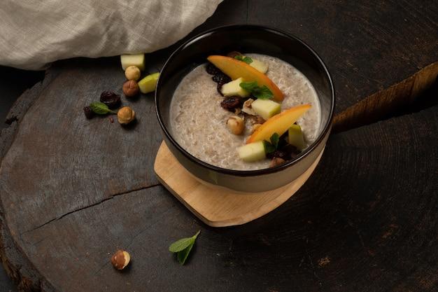 과일, 견과류 및 말린 과일과 함께 우유로 조리 한 오트밀. 깊은 세라믹 그릇에 맛있고 건강한 아침 식사 제공