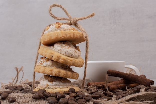 Овсяное печенье, чашка чая, корица и кофейные зерна на мешковине.