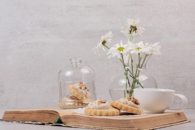 책에 오트밀 쿠키, 컵 및 데이지.