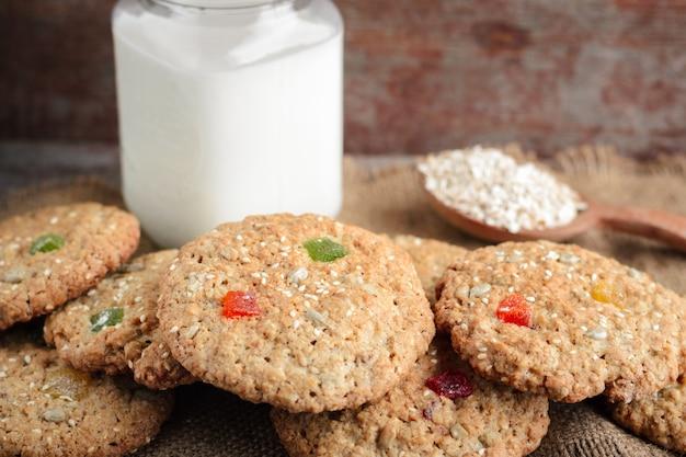 Овсяное печенье и стеклянная кружка с деревенским молоком на деревянном столе