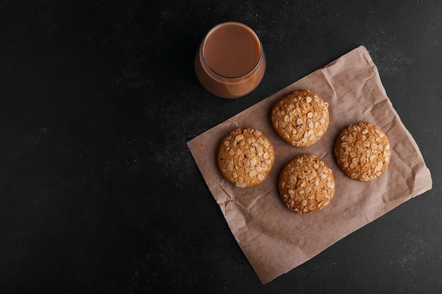 Oatmeal cookies on black background with a glass of hot chocolate, top view.