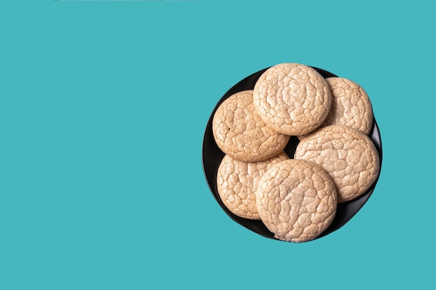 Oatmeal cookies in a black plate on a neo mint color background.