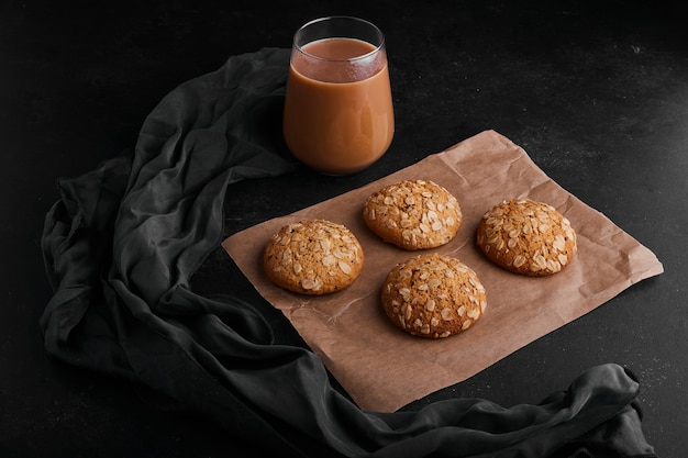 Oatmeal cookies on black surface with a glass of hot chocolate.
